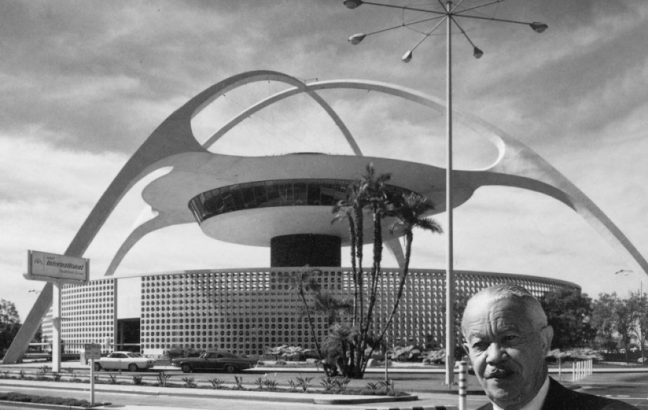 Paul R. Williams standing in front of the Theme Building in Los Angeles