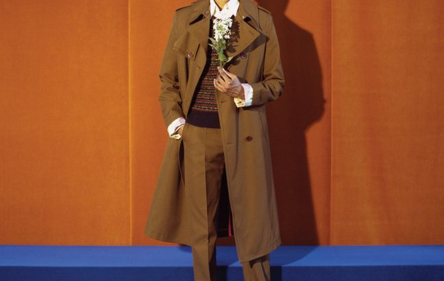 A man in a brown jacket, sweater, and trousers.