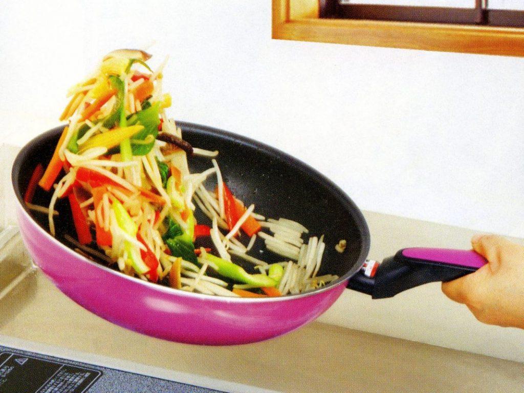someone making stir fry in a wok